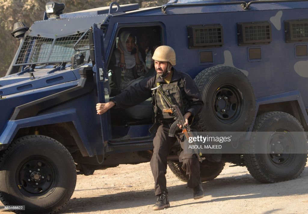 Pakistani police commando escort rescued staff members of an Agriculture Training Institute sit in a armoured vehicle after an attack by Taliban militants in Peshawar on December 1, 2017. Nine people were killed and dozens injured on December 1 when Taliban militants stormed a training institute in the northwestern city of Peshawar as Pakistan marked the birthday of the Prophet Mohammed, officials said. /