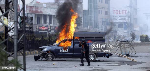 Pakistani police commando is seen alert beside a buring police van which was set on fire by protesters after security forces launched a crackdown on...