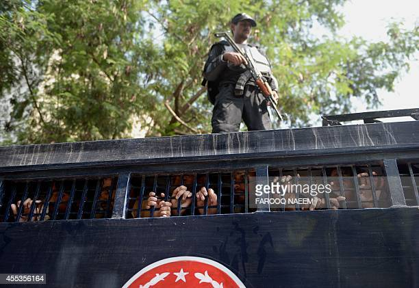 A Pakistani police commando stands guard on a prison van carrying detained opposition workers during a protest in Islamabad on September 13 2014 A...