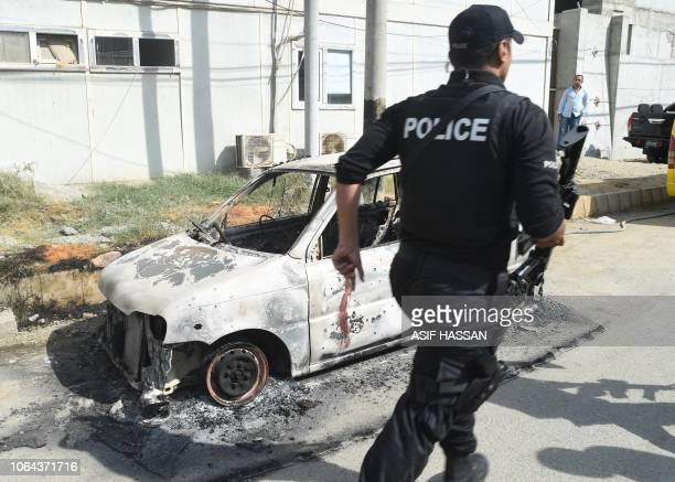 A Pakistani police commando walks past a burned out vehicle outside the Chinese consulate after an attack in Karachi on November 23 2018 At least two...