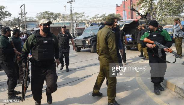Pakistani police commandos escort a police van carrying a suspect accused of raping and murdering a young girl as they arrive at an antiterrorist...