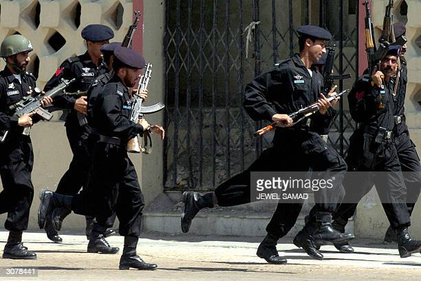 Pakistani police commandos run before a bus transporting the Indian cricket team upon their arrival at Jinnah International Airport in Karachi 12...