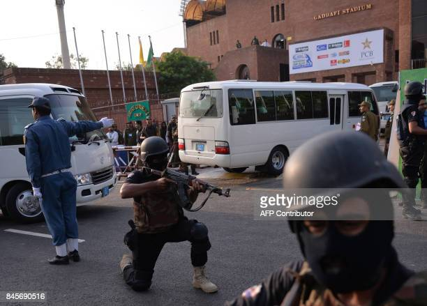 Pakistani police commandos take position as they escort a street on the arrival of International World XI players for practice at the Gaddafi Cricket...