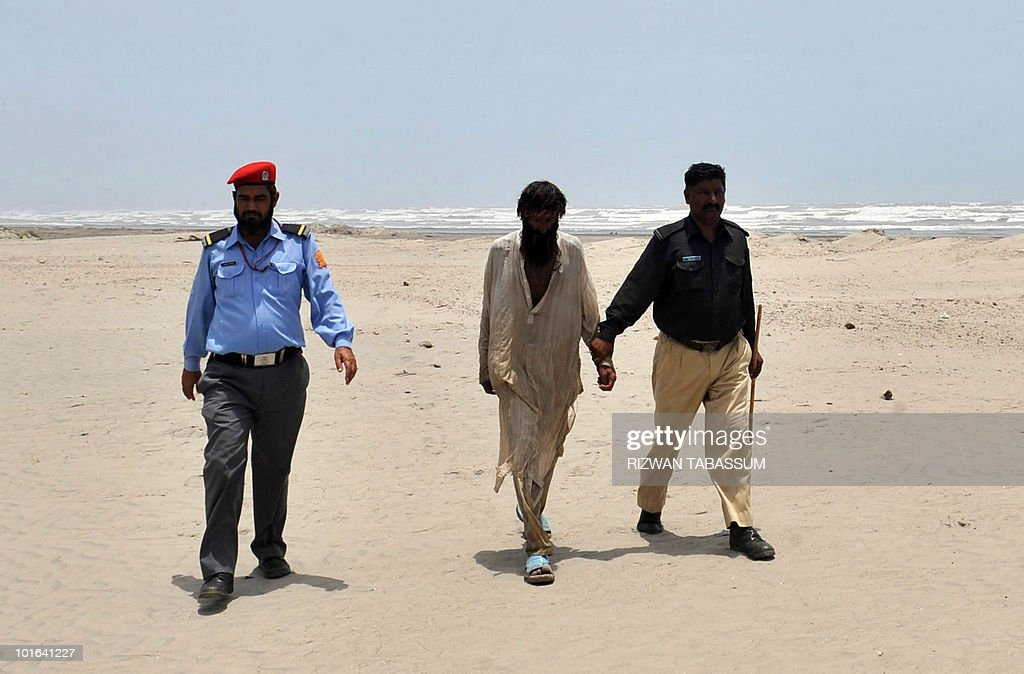 Pakistani police detain a man on the popular Seaview Beach for violating a beach curfew in Karachi on June 5, 2010. Pakistan issued a danger warning on June 4 over Cyclone Phet, which may hit the coast packing winds of 120 kilometres an hour, as relief workers were on standby to evacuate residents forcibly if needed. AFP PHOTO/Rizwan TABASSUM