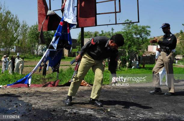 Pakistani police examine the site of a suicide bomb attack in the town of Swabi located about 100 kilometres east of Peshawar on March 30 2011 Six...