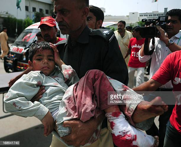 A Pakistani police officer carries an injured blast victim at a hospital following a bomb explosion in Karachi on May 11 2013 A Taliban bomb attack...