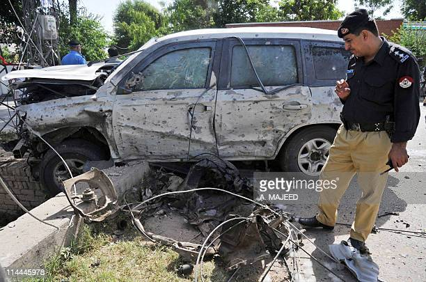 A Pakistani police officer looks at the wreckage of a US consulate vehicle after a car bomb blast in Peshawar on May 20 2011 A car bomb targeted US...