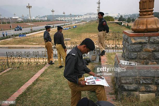 Pakistani police officer reads the morning newspaper near the presidential palace on November 4 2007 in Islamabad Pakistan On Saturday the government...