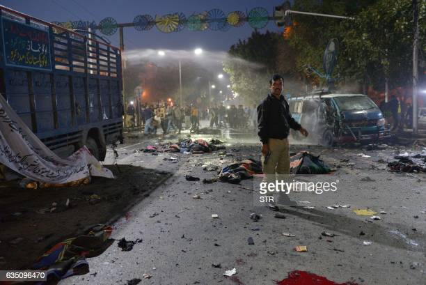 Pakistani police officer stands alert beside the bodies of victims at the site after a powerful explosion in Lahore on February 13 2017 At least 10...