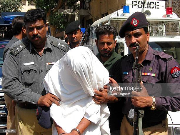 Pakistani police officers escort a head covered man named Sharib to a court September 21 2002 in Karachi Pakistan The Pakistan men are accused of...