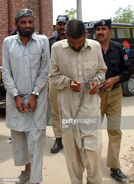 Pakistani police officers escort brothers Mohammad Arif and Farman Ali suspected of cannibalism to a local court in Sargodha on April 15 2014...