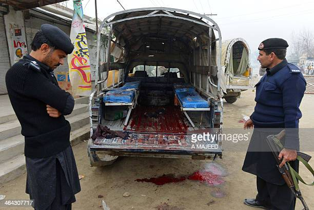 Pakistani police officers stand next to a bloodstained police vehicle after a bomb attack in Sir Dheri some 30 kilometres north of the main...