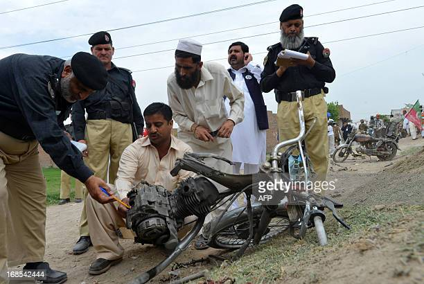 Pakistani police officials emaine a destroyed motorbike after a bomb explosion in Peshawar on May 11 2013 Bomb attacks wounded 12 people outside...