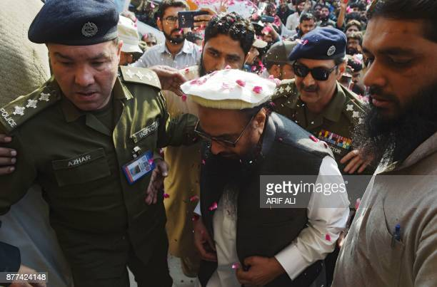 Pakistani police officials escort the head of the JamaatudDawa organisation Hafiz Saeed as he arrives at a court in Lahore on November 22 2017 A...