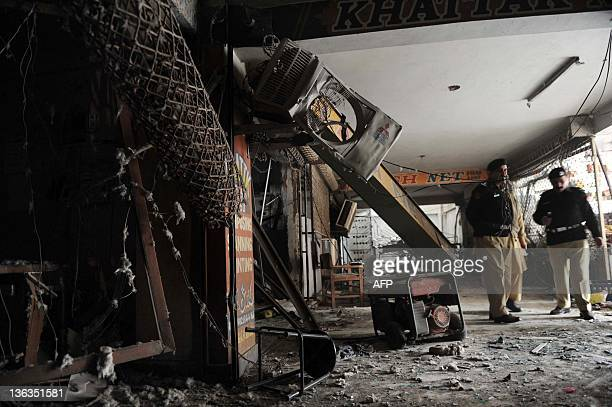 Pakistani police officials examine a damaged market following a bomb blast in Peshawar on January 3 2011 Two separate bomb blasts in Pakistan's...