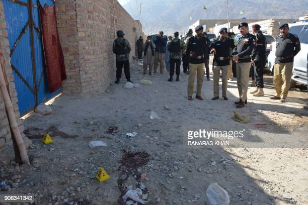 Pakistani police officials gather at the site of an attack by gunmen on a polio vaccination team on the outskirts of Quetta on January 18 2018 A...