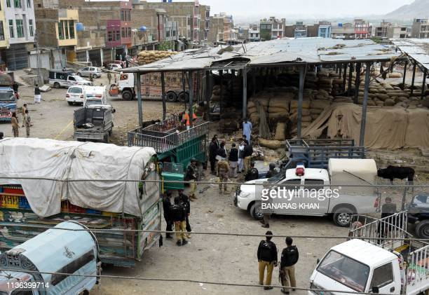 Pakistani police officials inspect the site of a bomb blast at a fruit market in Quetta on April 12 2019 At least 16 people were killed and 30...