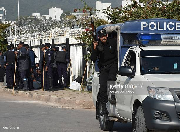 A Pakistani police personnel prepares to disembark from a vehicle during an antigovernment rally by opposition party Pakistan TehreekeInsaf in...