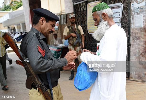 Pakistani police search devotees as they prepare to offer prayers on the last Friday of Ramadan ahead of the Eid alFitr holiday in Karachi on July 17...