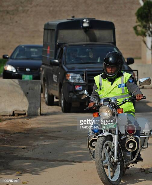 A Pakistani police squad escorts the car transporting Judge Rana Nisar Ahmad after the case hearing of assassination of exprime minister Benazir...