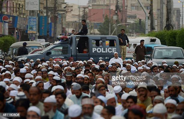 Pakistani police stand guard as devotees offer Eid prayers at the start of the Eid alFitr holiday marking the end of Ramadan outside a mosque in...