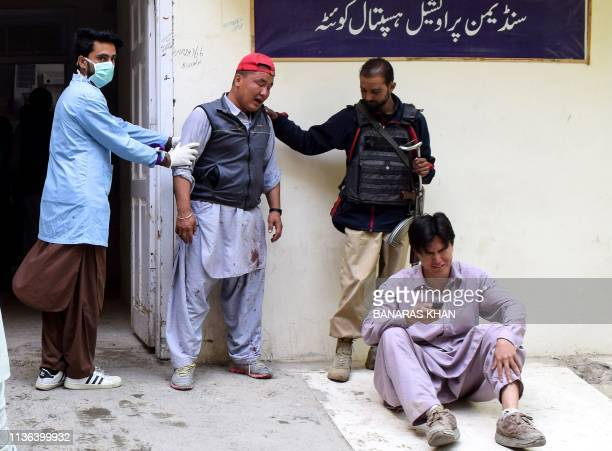 A Pakistani policeman and a medical staff member comfort mourners outside the mortuary following a bomb blast at a fruit market in Quetta on April 12...