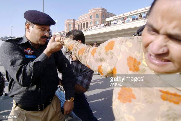 Pakistani policeman arrests a female party activist of the Pakistan Peoples Party outside the Allama Iqbal International Airport in the eastern...