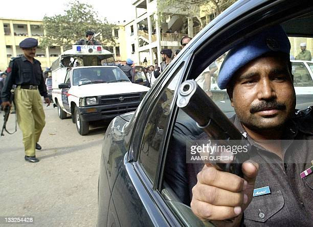 A Pakistani policeman brandishes a gun as while waiting to escort Fahad Naseem one of the accused in the kidnapping of US journalist Daniel Pearl...