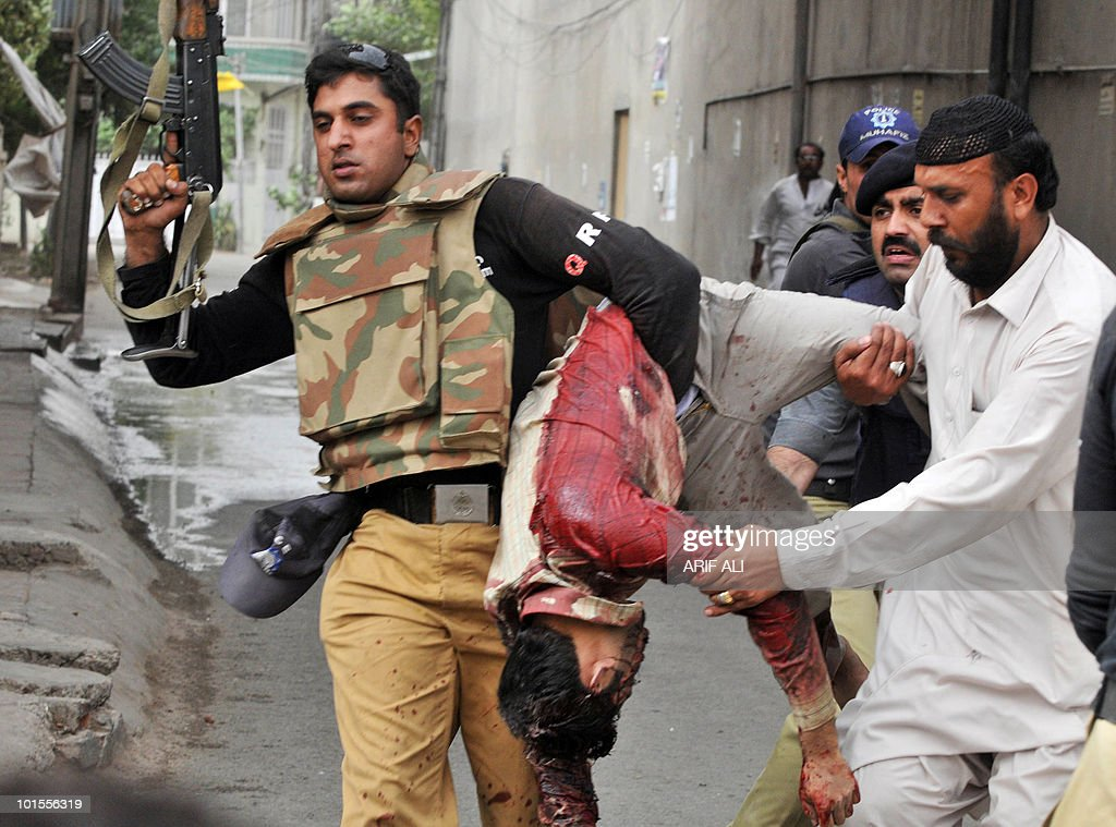 A Pakistani policeman carries the bloodied body of a worshiper at one of two mosques stormed by gunmen in Lahore on May 28, 2010. At least 56 people were killed when gunmen wearing suicide vests and carrying grenades attacked two mosques in the Pakistani city of Lahore on May 28, said police and an administration official. Gunfire and blasts rang out as the attackers, at least one of whom wore a suicide vest, stormed a mosque in the upscale neighbourhood Model Town and another in the busy Garhi Shahu area as people gathered for Friday prayers.