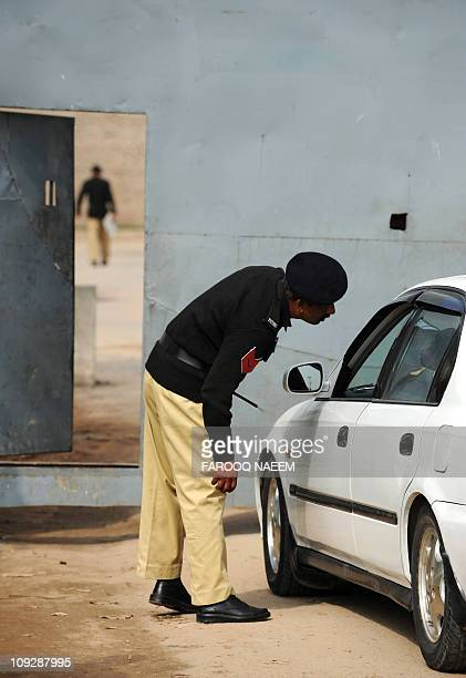 A Pakistani policeman checks the identity of lawyers before allowing entry to the Adiala prison during the case hearing concerning the assassination...