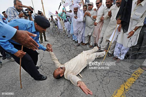A Pakistani policeman drags a government school teacher as they try to cross barbed wire during a demonstration in front of the Parliament House in...