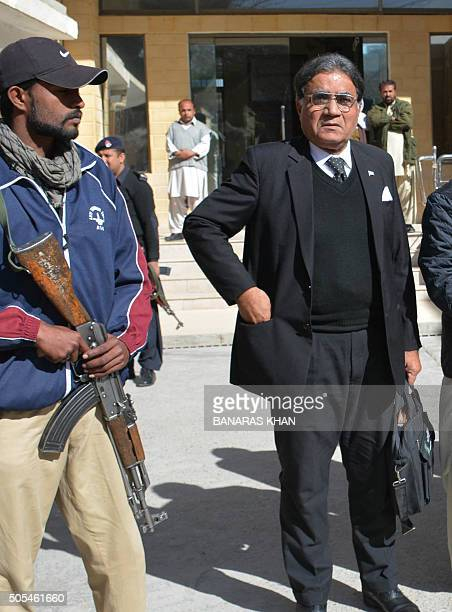 A Pakistani policeman escorts a lawyer for former Pakistani military ruler Pervez Musharraf Syed Akhtar Shah as he leaves after a court hearing in...