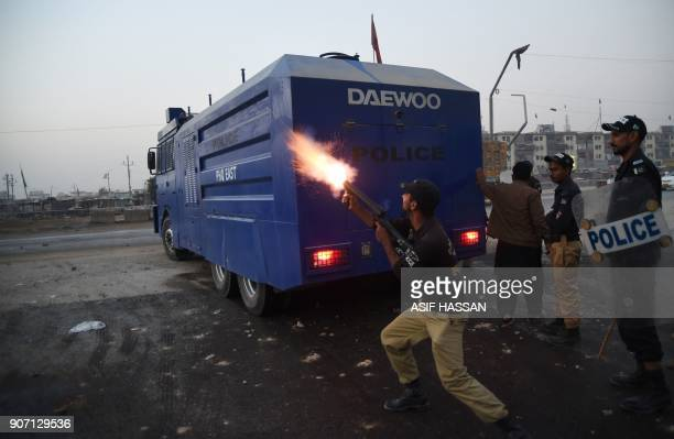 A Pakistani policeman fires a teargas shell towards demonstrators during a protest against the killing of a Naqeebullah in an alleged police...