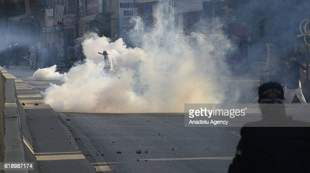 Pakistani policeman fires teargas shells at stonethrowing supporters of opposition party of TehreekeInsaaf of Imran Khan during a clash in Rawalpindi...