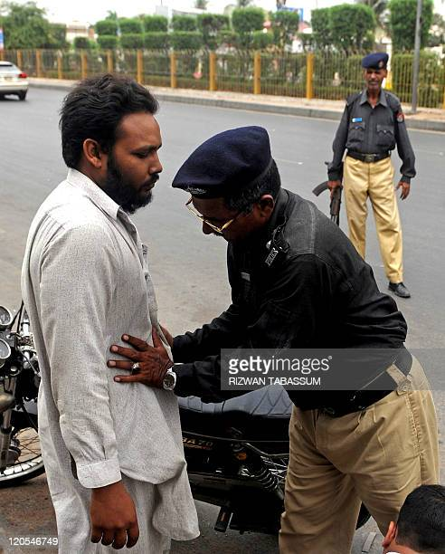 A Pakistani policeman frisks a motorcyclist at a security check point in Karachi on August 7 2011 Ethnic and politically linked violence in...
