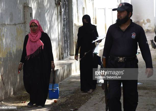 A Pakistani policeman guard to a polio health team during a polio vaccination campaign in Karachi on January 22 2018 A mother and daughter polio...