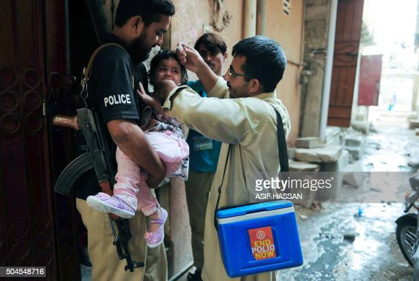 A Pakistani policeman holds a young girl as a health worker administers polio drops during a polio vaccination campaign in Karachi on January 11 2016...