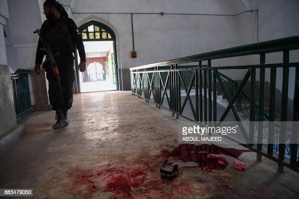 A Pakistani policeman looks a bloodstained floor of an Agriculture Training Institute following an attack by Taliban militants in Peshawar on...