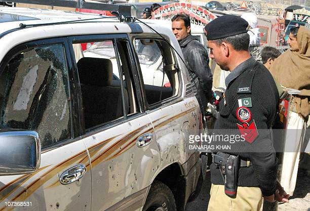 A Pakistani policeman looks at the damaged car from the chief minister's convoy after a suicide attack in Quetta on December 7 2010 A suicide attack...