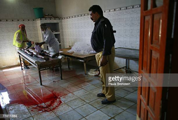 A Pakistani policeman looks on as a dead body is washed at the Edhi Morgue October 19 2007 in Karachi Pakistan A suicide bombing killed at least 136...