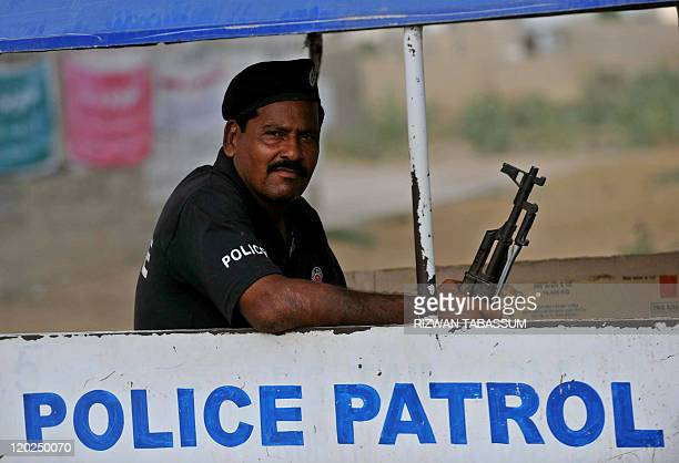 A Pakistani policeman patrols atop a police van in the troubled area of Karachi on August 2 2011 At least 35 people were killed in 24 hours in...