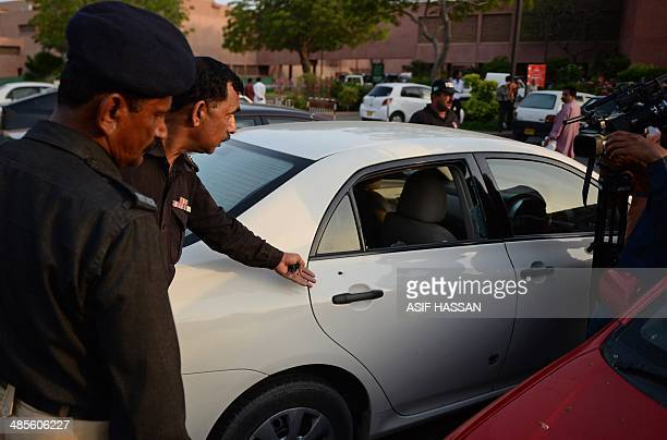 A Pakistani policeman points to a bullet hole ront on a car door following an attack on prominent Pakistani journalist Hamid Mir in Karachi on April...