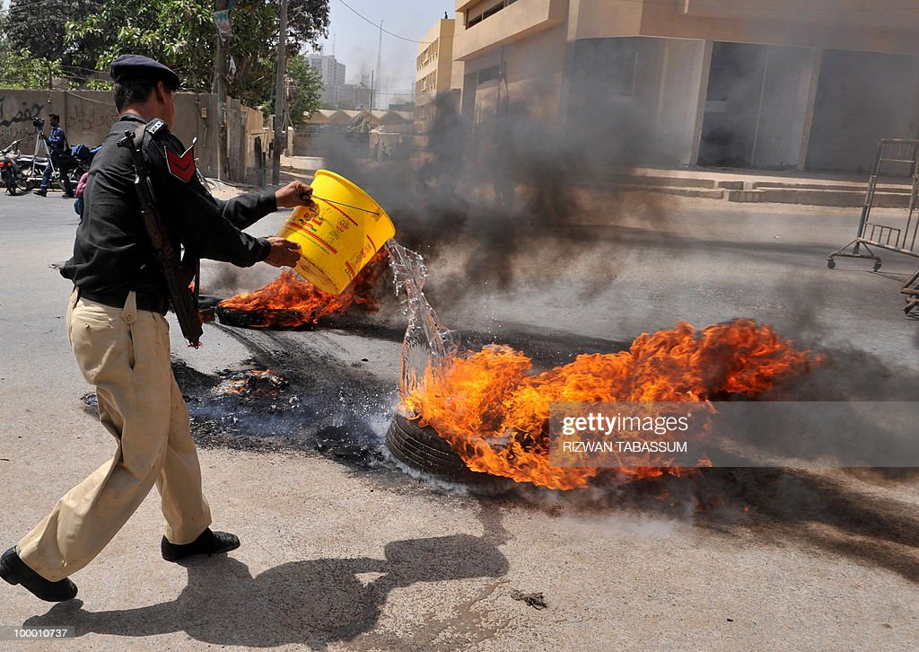 A Pakistani policeman pours water over burning tyres torched by an angry mob during a protest against alleged target killings in Karachi on May 20, 2010. At least 17 people including two children have been killed in political clashes in Pakistan's financial capital Karachi in the past two days, a government official and police said. Police and paramilitary have been put on high alert and authorities closed all schools and colleges after the latest outbreak of politically related violence in Karachi, the biggest and richest city in Pakistan.