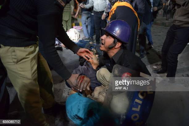 A Pakistani policeman reacts as he attempts to move an injured victim from a blast site after a powerful explosion in Lahore on February 13 2017 A...