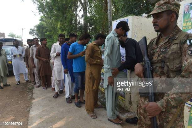 Pakistani policeman search voters outside a polling station in Lahore on July 25 2018 Polls opened July 25 in a tense unpredictable Pakistani...