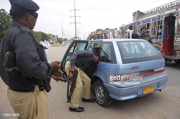 A Pakistani policeman searches a car in a troubled area of Karachi on August 3 2011 At least 35 people were killed in 24 hours in Karachi as...