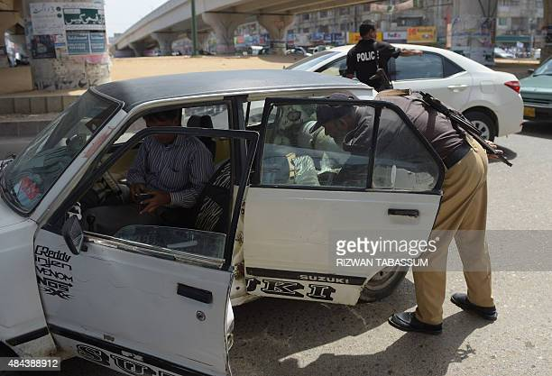 A Pakistani policeman searches a vehicle at a checkpoint following an attack on Muttahida Qaumi Movement opposition party legislator Rashid Godil in...