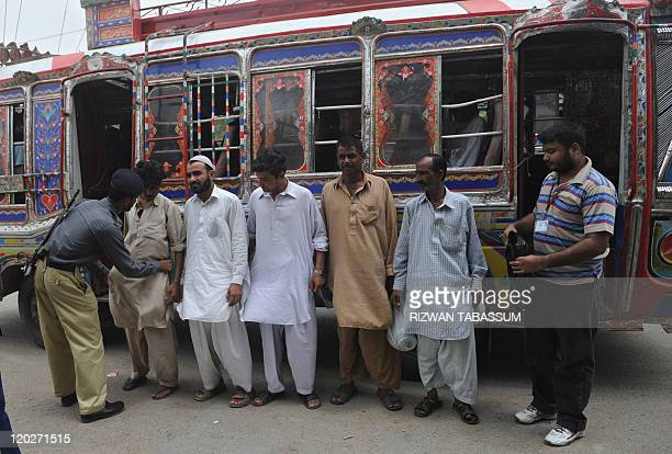 A Pakistani policeman searches passengers from a bus in a troubled area of Karachi on August 3 2011 At least 35 people were killed in 24 hours in...
