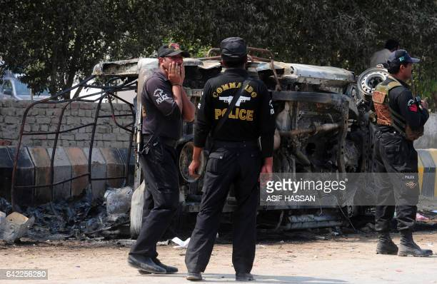 Pakistani policeman stand beside a burnt out a police vehicle torched by mourners during a protest against bomb attack on a shrine of 13th century...