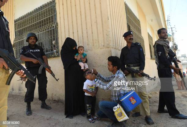 TOPSHOT Pakistani policeman stand guard as a health worker administers polio drops to a child during a polio vaccination campaign after a day of an...